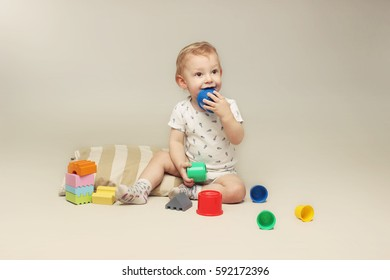 Studio portrait of cute little baby boy sitting on the floor and playing with some toys.