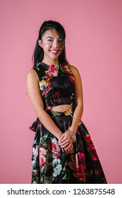 Studio portrait of a cute, petite, young and attractive Singaporean Chinese woman in a black dress against a pink background. She is cheerful, confident and smiling.