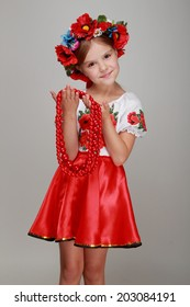 Studio portrait of cute smiling little girl in a beautiful national costume of Ukraine holds red beads on a gray background on Beauty and Fashion