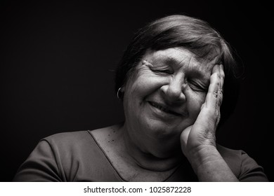 Studio portrait of elderly woman with hands near the face. Smile. Toned.