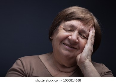 Studio portrait of elderly woman with hands near the face. Smile.