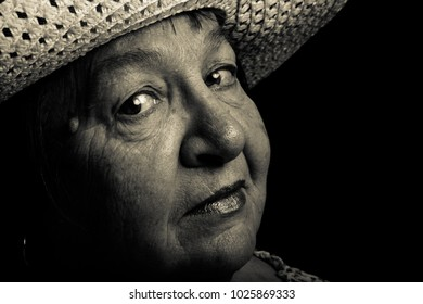 Studio portrait of elderly woman with hat. Coquetry. Toned.