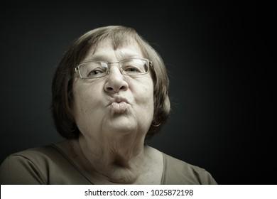 Studio portrait of elderly woman. Kiss. Toned.