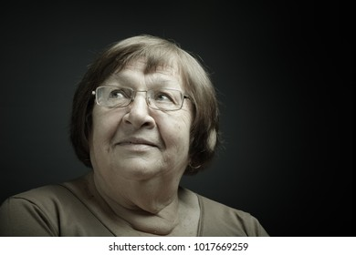 Studio portrait of elderly woman. Smile. Toned.