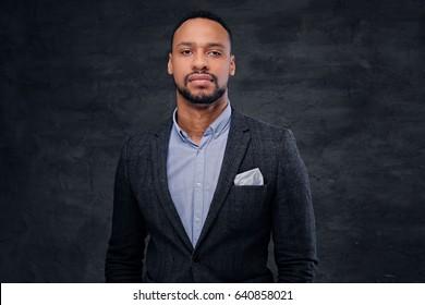 Studio portrait of elegant black American male dressed in a suit over grey vignette background.