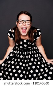 studio portrait of emotional young woman in polka-dot dress over dark background
