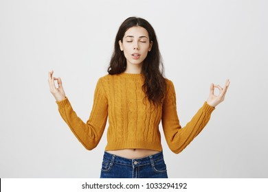 Studio portrait of expressive young slim female meditating, spreading hands with zen gesture, being calm while standing over gray background with closed eyes and half-opened mouth. Girl tries to relax