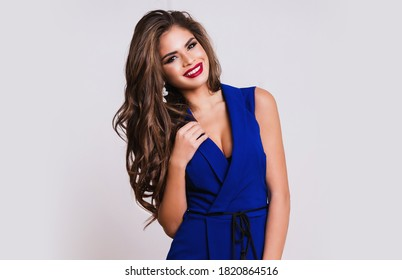 Studio portrait of fashion model with beautiful face and perfect body. Decollete on  short blue party dress, open arms. Stylish makeup and curly hair.