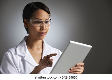 Studio Portrait Of Female Laboratory Worker With Digital Tablet