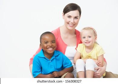 Studio Portrait Of Female Pre School Teacher With Pupils