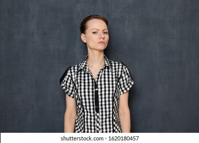 Studio portrait of focused thoughtful self-confident young blond woman wearing checkered shirt, looking haughtily and seriously at camera, holding arms along the body, standing aganst gray background