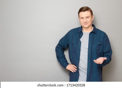 Studio portrait of friendly man wearing blue shirt, smiling, stretching one hand like offering product, asking your opinion or waiting your decision, standing over gray background, copy space on left