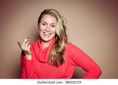 Studio portrait in front of beige background of blonde woman smiling