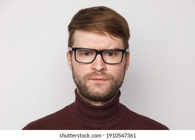 studio portrait of a frowning guy on a light background