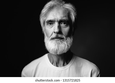 Studio portrait of frowning senior man with gray beard.