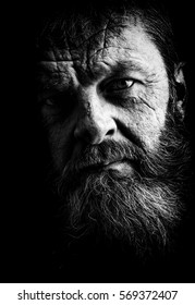 Studio portrait of fully bearded man in black and white.  Closeup face with facial expression.
