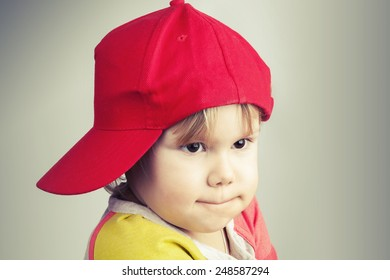 Studio portrait of funny baby girl in red baseball cap over gray wall background. Vintage style, instagram toned photo filter effect