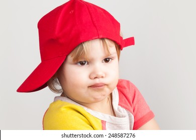 Studio portrait of funny confused baby girl in red baseball cap over gray wall background