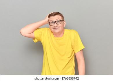 Studioporträt eines lustigen, verwirrten, blonden Mannes mit gelbem T-Shirt, Haltungen auf dem Kopf, Lächeln verwirrt, Schultern zucken, wie dummer Benutzer aussehen, auf grauem Hintergrund stehen
