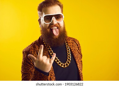 Studio portrait of funny eccentric rich bearded chubby young man in sunglasses, extravagant funky outfit and huge gold chain around neck doing rock horn sign, looking at camera and sticking tongue out