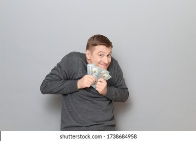Studio portrait of funny happy mature man wearing casual jumper, holding bunch of US dollars in hands, clasping money to his chest, looking greedy and sly, standing hunched over gray background