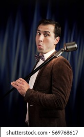 Studio portrait of a funny showman with the microphone