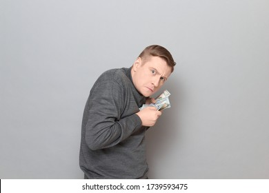 Studio portrait of funny worried mature man wearing jumper, holding bunch of US dollars in hands, clasping money to his chest, looking greedy and incredulous, standing hunched over gray background