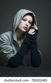 Studio portrait of a girl in a hoodie on a dark background