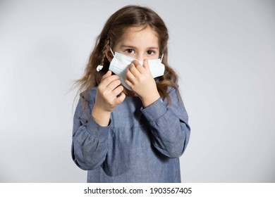 Studio portrait of girl wearing a face mask, looking at camera, close up, isolated on gray background. Flu epidemic, dust allergy, protection against virus. High quality photo