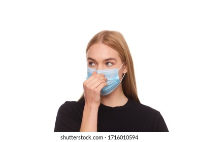 Studio portrait of a girl who holds out a medical mask on her face. Virus protection. Isolated on white background, close up.