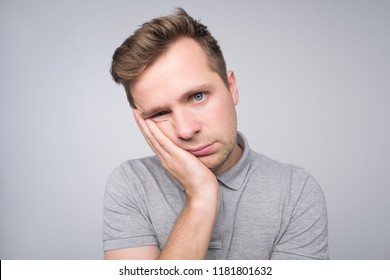 Studio portrait of gloomy bald european man showing boredom while leaning head on hand and standing over gray background. I am not interested in all this stupid rumors.