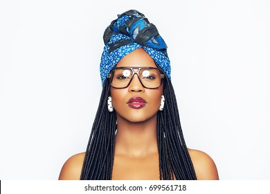 Studio portrait of gorgeous African-American attractive woman in goggles and traditional turban looking at camera.