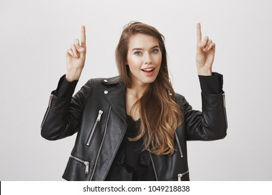 Studio portrait of gorgeous feminine woman in leather jacket pointing upwards with raised index fingers, smiling joyfully, being intrigued and interested at copy space, standing over gray background