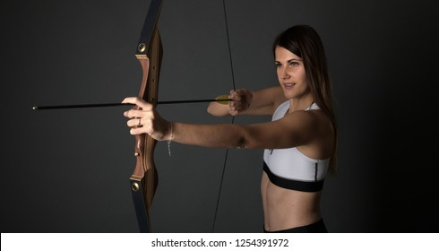 Studio portrait of a gorgeous young long haired female holding bow. Archery. Bowman.