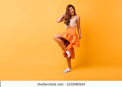 Studio portrait of graceful girl in orange skirt dancing with smile. Blithesome ginger lady having fun on yellow background.
