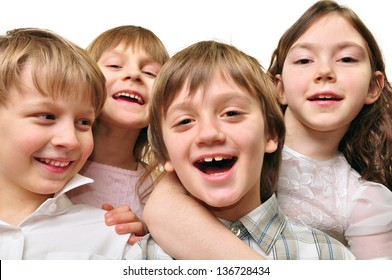 Studio portrait of a group of four happy smiling elementary age children. Best friends. Isolated over white.