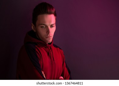 Studio portrait of a guy in a hooded sweater without looking at the camera. Close up using red backlight.