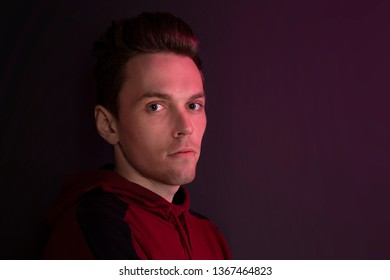 Studio portrait of a guy in a hooded sweater. Close up using red backlight.