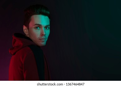 Studio portrait of a guy in a hoodie. Close-up, using green and red back lights.