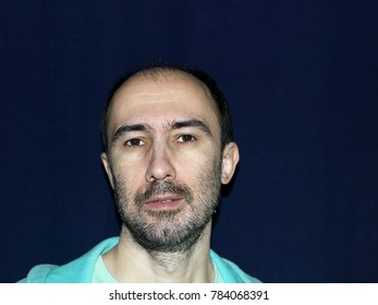 Studio portrait of a guy with mocking look on his unshaven face