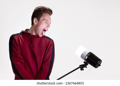 Studio portrait of a guy who grimaces in the studio holding a spotlight in his hands. On the white background.