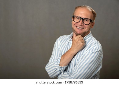 Studio portrait of a handsome cheerful smiling mature man with glasses and a beard.