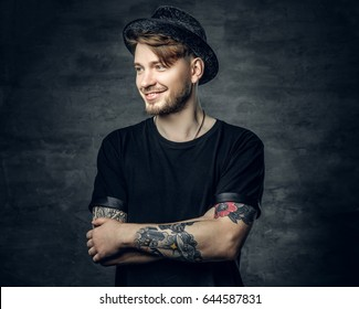 Studio portrait of handsome male with crossed tattooed arms, dressed in a black t shirt and tweed hat.