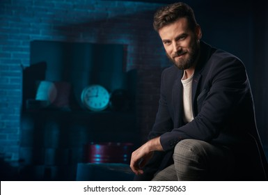 Studio portrait of handsome man with dark hair, beard and mustache wearing dark blue jacket, gray pants. Blue lighted brick background with clock and barrel