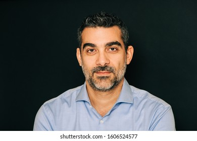 Studio portrait of handsome man wearing formal blue shirt, posing on black background