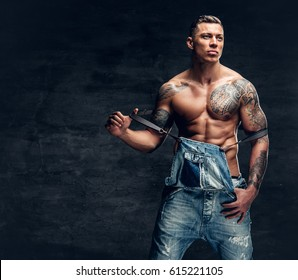 Studio portrait of handsome muscular male fitness model with tattoo on a chest dressed in a jeans.