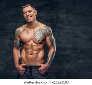 Studio portrait of handsome muscular shirtless male fitness model with tattoo on his chest.