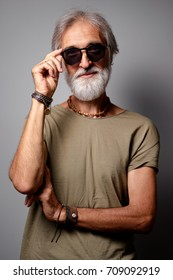 Studio portrait of handsome senior man with gray beard and sunglasses.