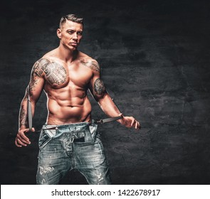 Studio portrait of handsome shirtless muscular, athletic male with a tattoo on his chest dressed in a jeans.