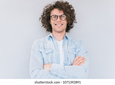 Studio portrait of handsome smart-looking smiling male posing for advertisement wears denim shirt and round glasses, isolated on white wall with copy space for your informational text. People race